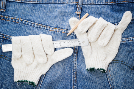 ruler, pencil on glove, blue jeans background for repair  restore tools DIY concept