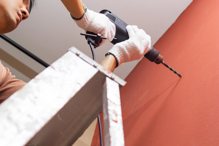 hands holding electric drill on ladder, interior design and home renovation DIY concept