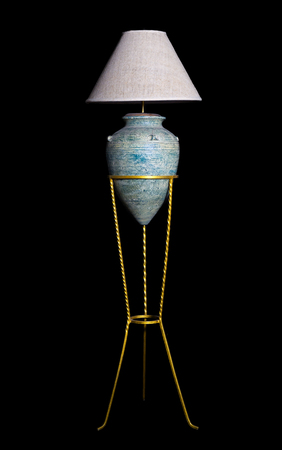 antique green pottery lamp on gold classical stand, isolated on black for interior concept 스톡 콘텐츠
