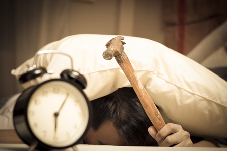 sleeping asian young male disturbed by alarm clock early morning on bed & holding hammer in hand