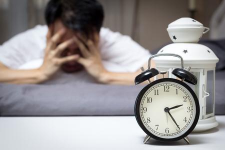 夜彼の問題について考えて不眠症と睡眠障害に苦しんでいるベッドのアジア人男性