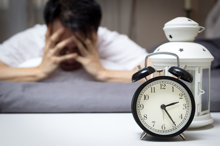 asian man in bed suffering insomnia and sleep disorder thinking about his problem at night Standard-Bild