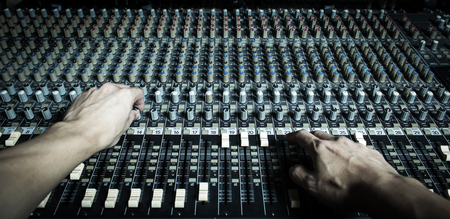 voices: hands of sound engineer working on recording studio mixer Stock Photo