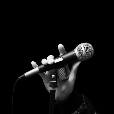 singer right hand holding dynamic microphone, bw filter & isolated on black.hand sign mean love, love to sing