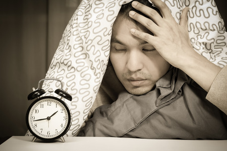 asian man in bed suffering insomnia and sleep disorder thinking about his problem at night Stock Photo