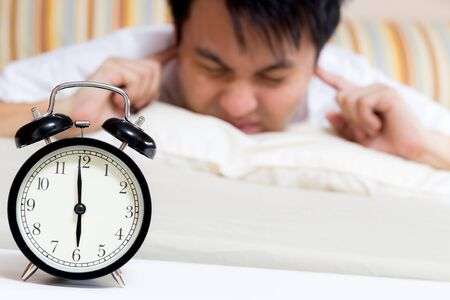 sleeping asian young male disturbed by alarm clock early morning on bed