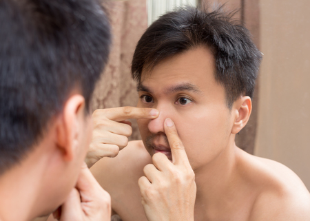 Mirror reflection of a young asian handsome man viewing his face