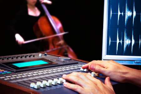 cellos: sound engineer hands working on digital sound mixer for cello recording Stock Photo