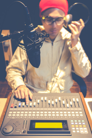 loud speaker: asian handsome DJ working in radio broadcasting studio Stock Photo