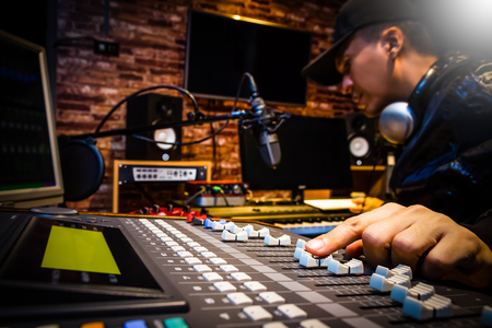 music producer working on sound mixer in recording studio or DJ working in broadcasting studio