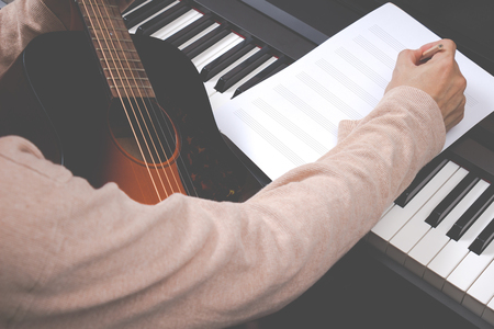 male songwriter writing song on blank music sheet