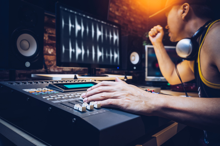 asian popular DJ working in radio broadcasting studio or music producer working in recording studio Foto de archivo