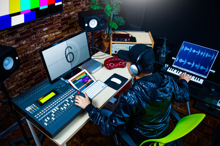 asian male sound engineer working in digital audio & video editing post production studio Stok Fotoğraf