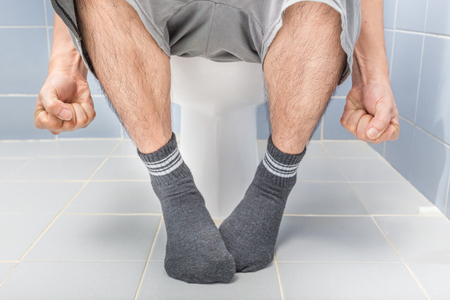 Man sitting on toilet, diarrhea Stock Photo