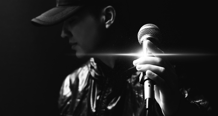 portrait of asian handsome singer posing on microphone, black and white Foto de archivo