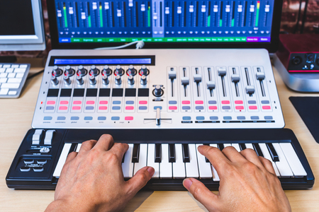 male musician hands playing midi keyboard synthesizer in recording studio