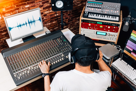 asian male music producer, sound engineer, composer, dj working in studio. recording, broadcasting, audio video editing concept Foto de archivo