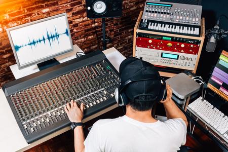 asiatischer männlicher Musikproduzent, Tontechniker, Komponist, DJ, der im Studio arbeitet. Aufnahme, Rundfunk, Audio-Video-Editing-Konzept