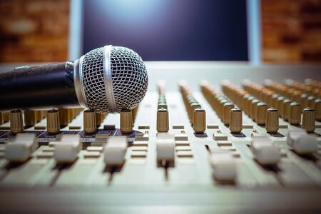 microphone on sound mixer with computer monitor background, shallow dept of field. focus on mic. music concept