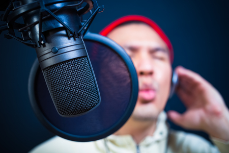 asian handsome male singer singing in recording studio or DJ chatting in radio station, nightclub. focus on condenser microphone