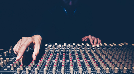 Male sound engineer hands working on audio mixing console in recording studio