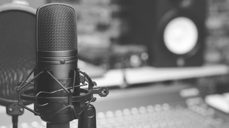 black and white condenser microphone on audio mixing board & studio monitor speakers background. recording concept Stock Photo