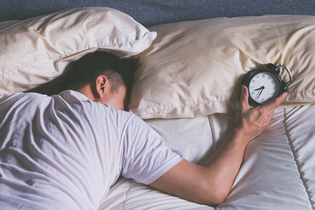 sleeping asian young male disturbed by alarm clock early morning in bed