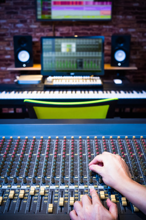 sound engineer hands working on audio mixing console in recording studio Stock Photo