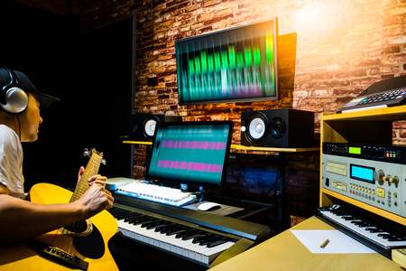 asian male musician recording acoustic guitar track on digital professional audio equipment in home studio