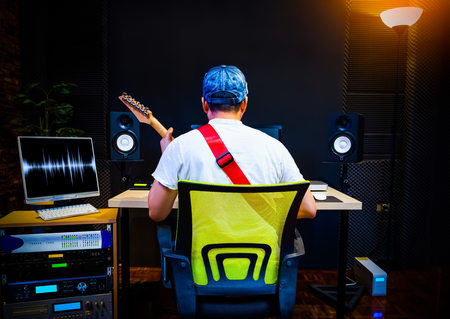 back of asian guitarist recording electric guitar in home studio