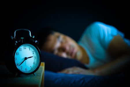 schlafender asiatischer Mann im Bett in der Nacht Standard-Bild
