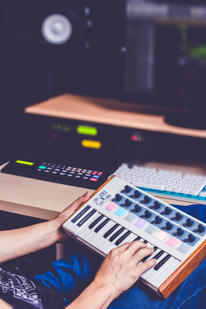 male producer hands playing keyboard for recording midi track on computer in home studio