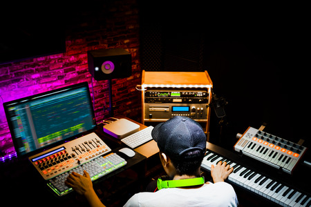 back of male asian producer working in sound design studio. music, film score, advertising footage digital editing, jingle song, voice actor recording, post production Stockfoto
