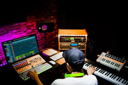 Rückseite eines männlichen asiatischen Produzenten, der im Sound-Design-Studio arbeitet. Musik, Filmmusik, digitale Bearbeitung von Werbematerial, Jingle-Song, Synchronsprecheraufnahme, Postproduktion Standard-Bild