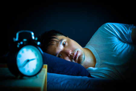asian man in bed suffering insomnia and sleep disorder thinking about his problem at night Фото со стока