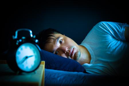 asiatischer Mann im Bett, der an Schlaflosigkeit und Schlafstörung leidet und nachts über sein Problem nachdenkt Standard-Bild