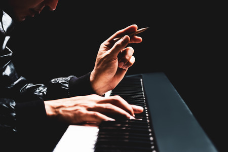 male songwriter hands composing a song on piano, song writing concept