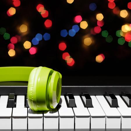 green headphone on piano keys, bokeh background