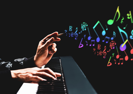 male songwriter hands composing a song on piano. song writing, music education concept