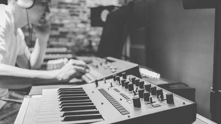 asian male composer making music in home studio