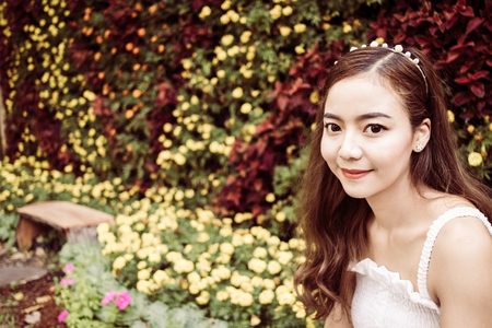 asian pretty woman smiling on beautiful flowers background