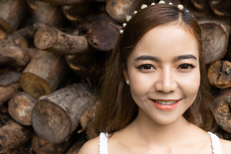 asian pretty woman smiling on stack of log background