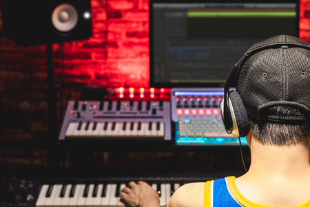 back of male asian music producer arranging a song in home recording studio