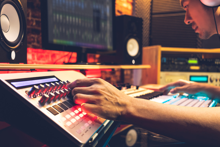 male DJ, producer, composer, sound engineer, editor working in sound studio, broadcasting studio, home studio for post production