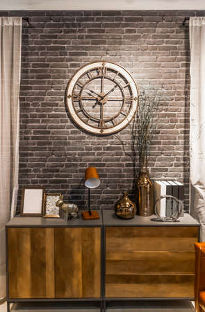 wooden retro style sideboard with vintage loft design clock on brick wall, decoration and interior concept