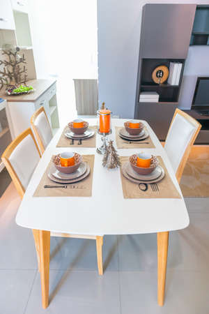 Dining table with contemporary tableware and festive decor in small kitchen