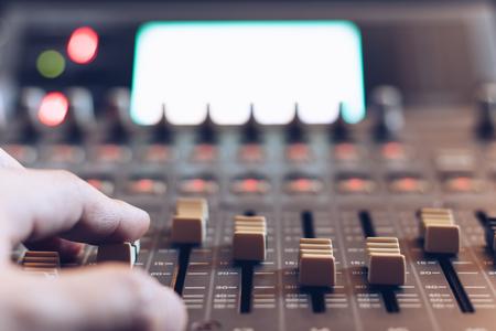 close up sound engineer, producer, dj hands adjusting sound mixer fader Imagens