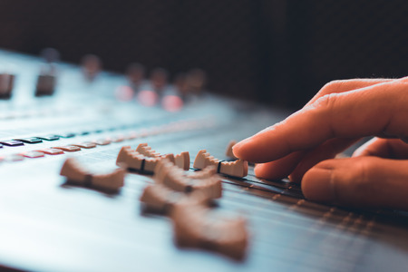 close up sound engineer, producer, dj hands adjusting sound mixer fader Stock Photo