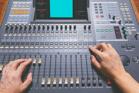 sound engineer hands working on sound mixing console in recording studio. music production, broadcasting concept