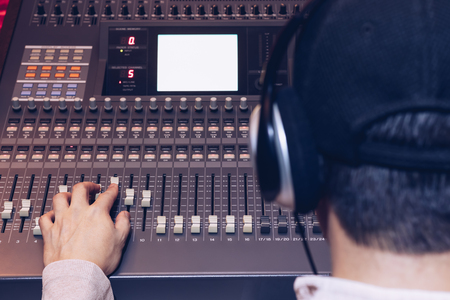 back of male sound engineer working on audio mixing console recording, editing, broadcasting studio. focus on hand